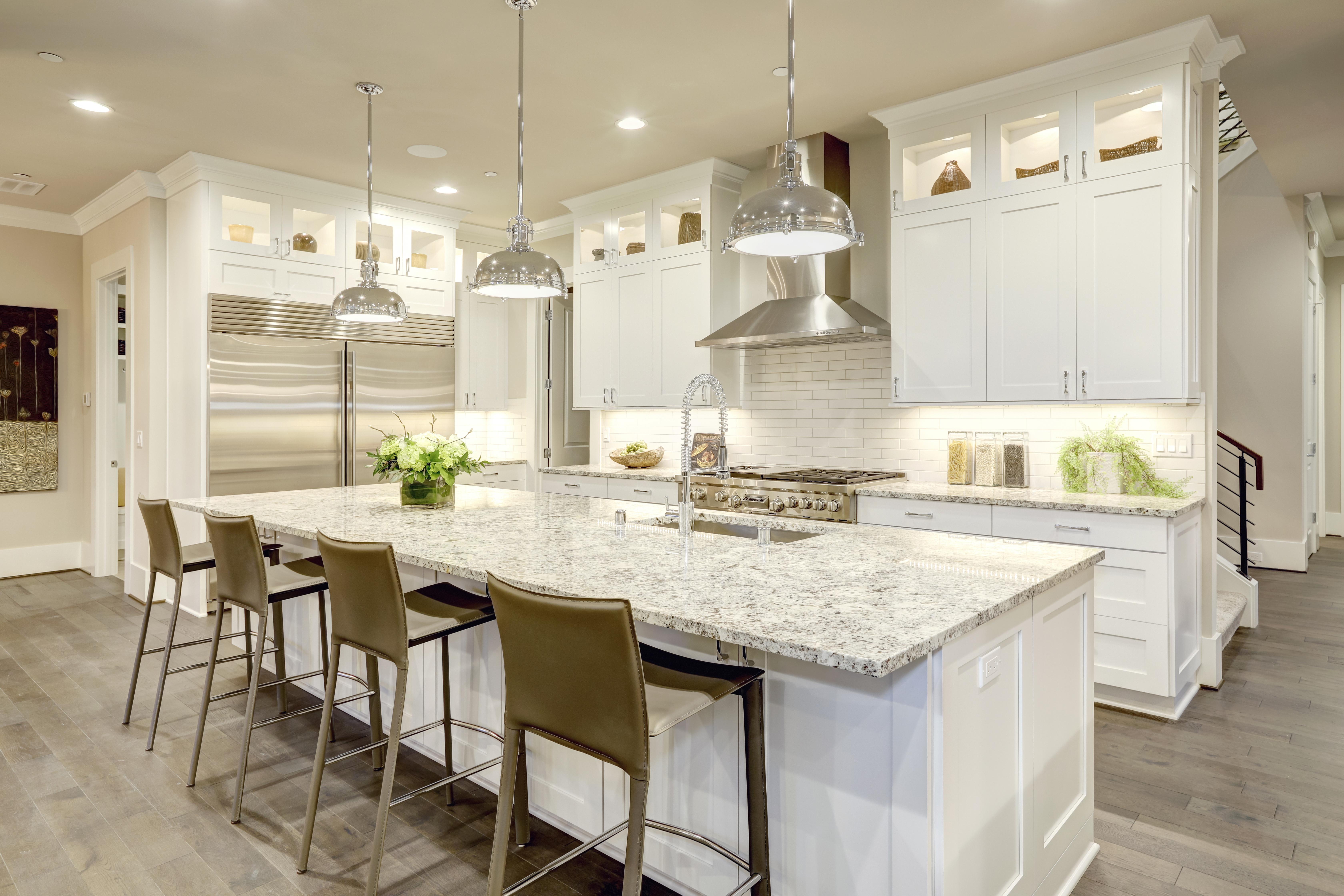 White kitchen design features large bar style kitchen island with granite countertop | Pierce Flooring