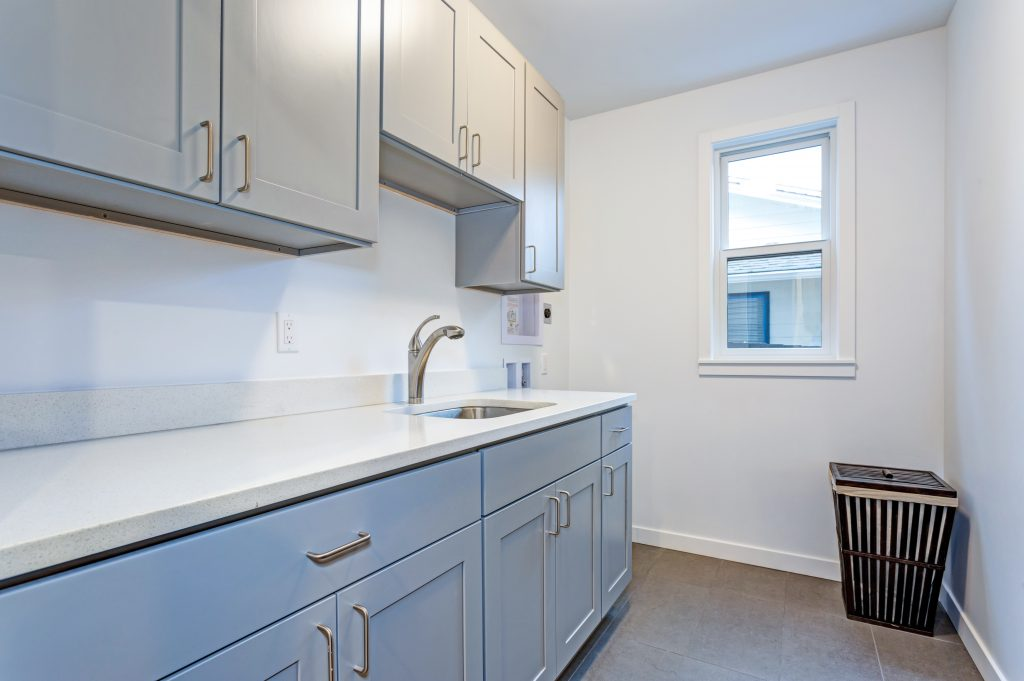 White laundry room with shaker cabinets and white quartz countertop   Pierce Flooring