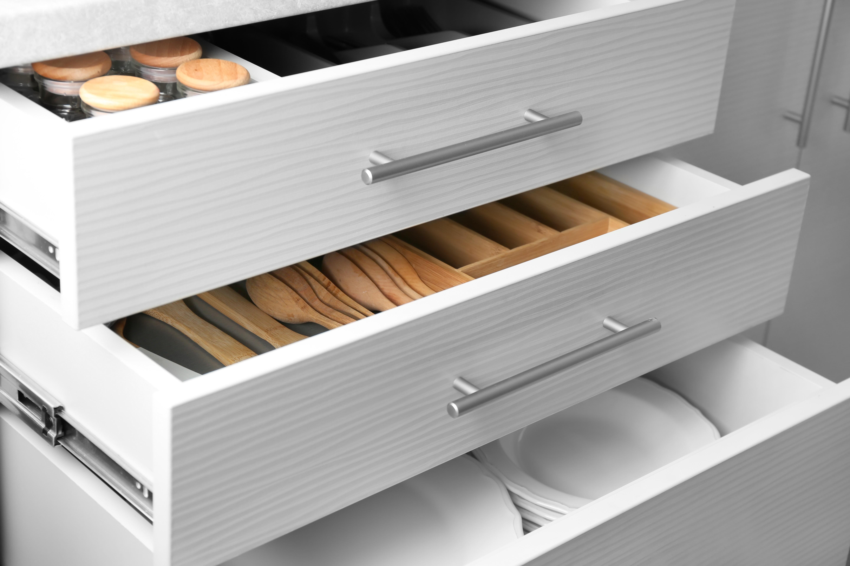 Set of ceramic plates and utensils in kitchen drawers | Pierce Flooring