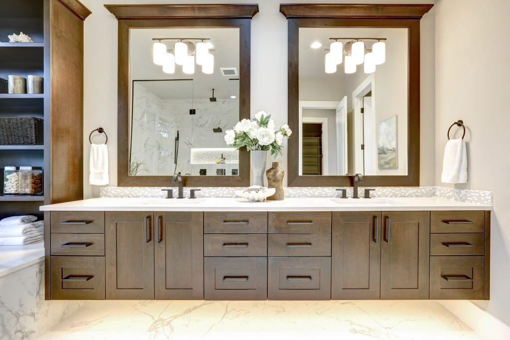 Master bathroom interior in luxury modern home with dark hardwood cabinets, white tub and glass door shower | Pierce Flooring