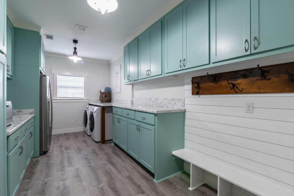 Mint green and white laundry room with mudroom, counter space, oversized   Pierce Flooring