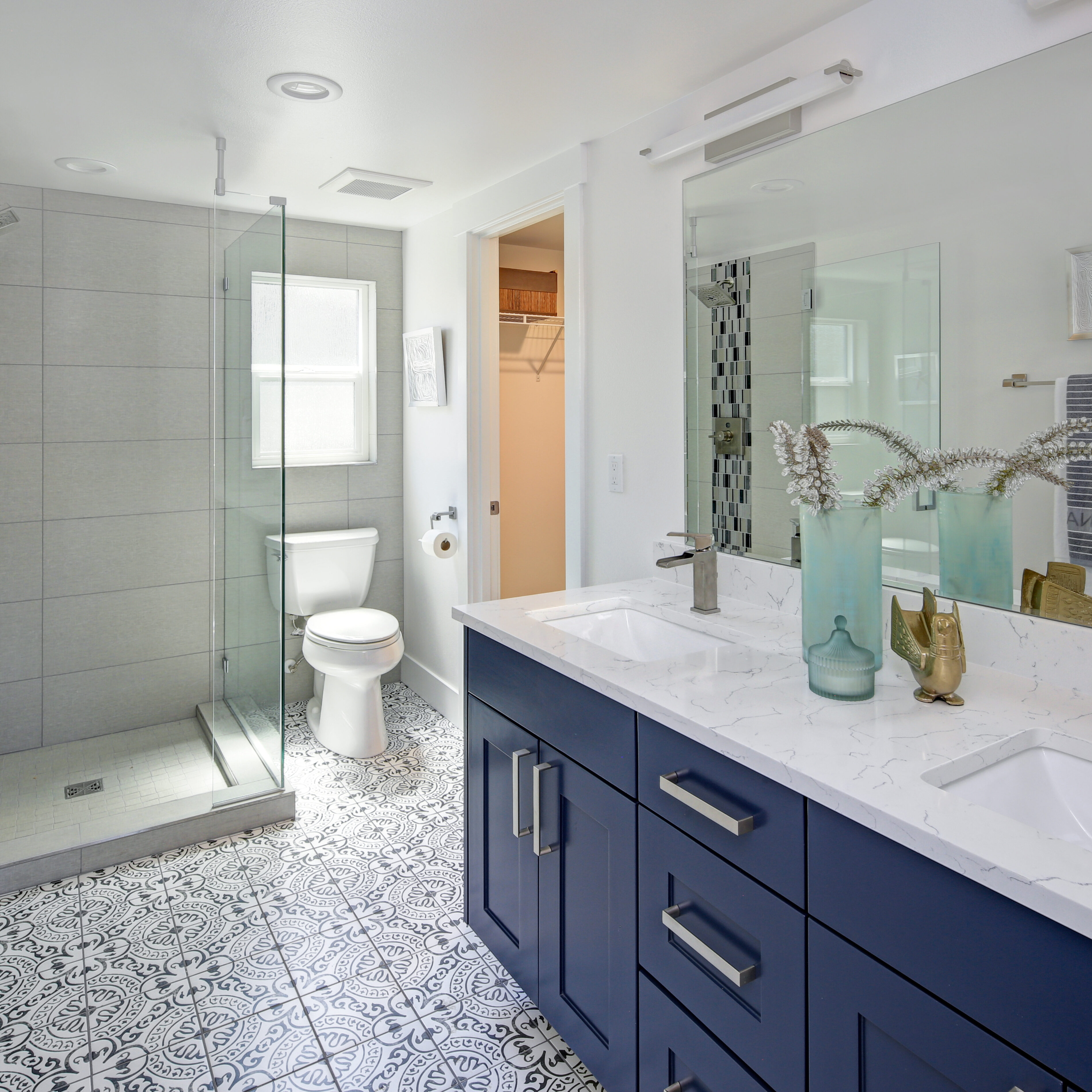 Modern bathroom interior with blue double vanity and glass shower | Pierce Flooring